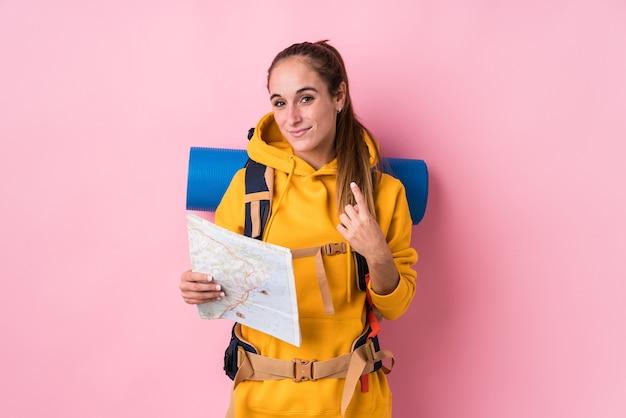 Jeune voyageur caucasien femme isolée pointant avec le doigt sur vous comme si vous invitiez à vous rapprocher.