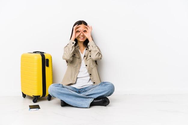 Jeune voyageur chinois femme assise tenant une carte d'embarquement montrant un signe correct sur les yeux