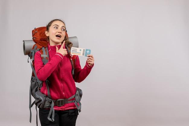 Jeune voyageur demandé avec un grand sac à dos tenant un billet de voyage avec lieu de copie