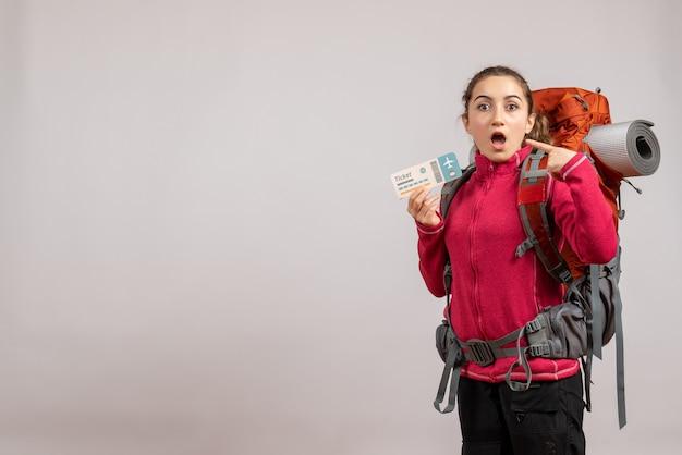 Jeune voyageur demandé avec sac à dos tenant un billet de voyage