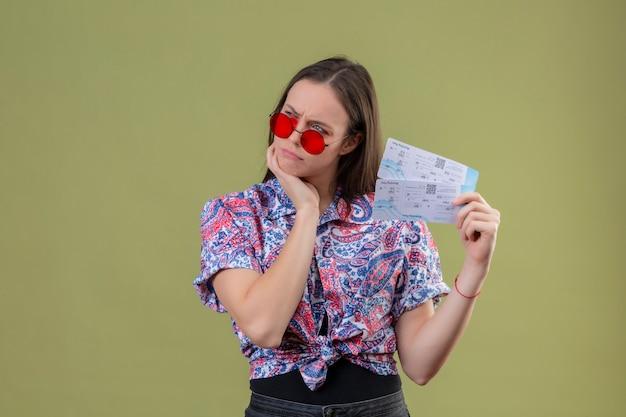 Jeune voyageur femme portant des lunettes de soleil rouges tenant des billets avec la main sur le menton mécontent et pensant avec expression pensive sur mur vert