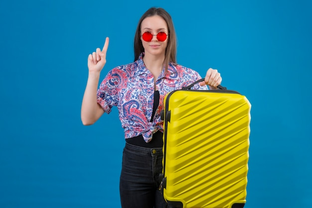Jeune voyageur femme portant des lunettes de soleil rouges tenant une valise jaune debout avec le doigt à la confiance d'avoir une bonne idée sur fond bleu