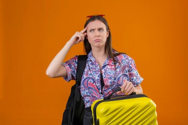 Jeune voyageur femme portant des lunettes de soleil rouges sur la tête debout avec sac à dos tenant la valise pointant le temple avec froncement de sourcils se souvient d'elle-même de ne pas oublier la chose importante debout sur oran