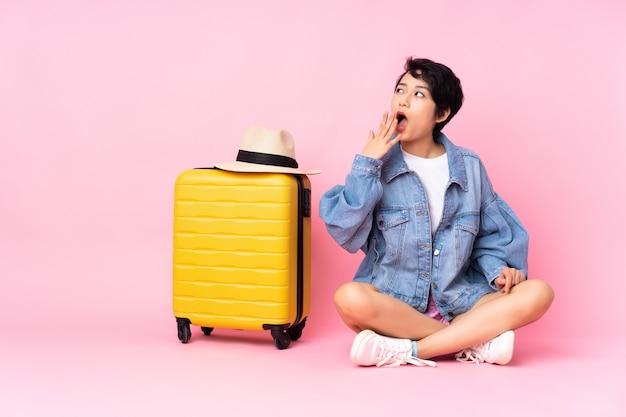 Jeune voyageur femme vietnamienne avec valise assis sur le sol sur le bâillement rose isolé et couvrant la bouche grande ouverte avec la main