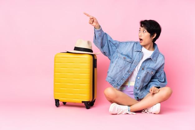 Jeune voyageur femme vietnamienne avec valise assis sur le sol sur un mur rose isolé pointant loin
