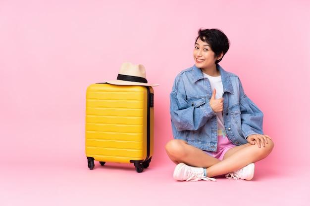 Jeune voyageur femme vietnamienne avec valise assis sur le sol sur rose isolé donnant un coup de pouce geste
