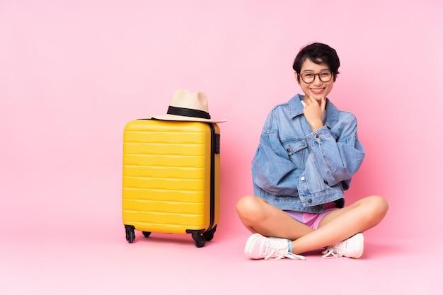 Jeune voyageur femme vietnamienne avec valise assis sur le sol sur rose isolé avec des lunettes et souriant