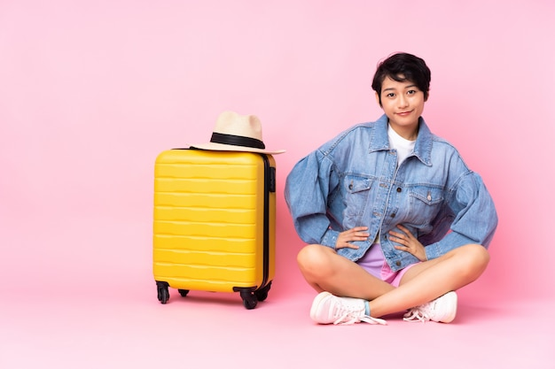 Jeune voyageur femme vietnamienne avec valise assis sur le sol sur rose isolé en position arrière
