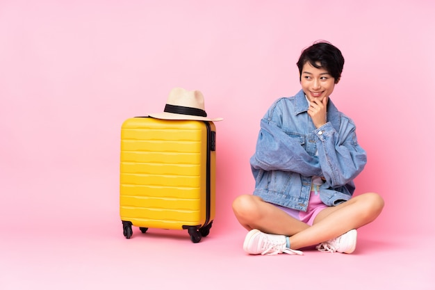 Jeune voyageur femme vietnamienne avec valise assis sur le sol sur rose isolé à la recherche sur le côté