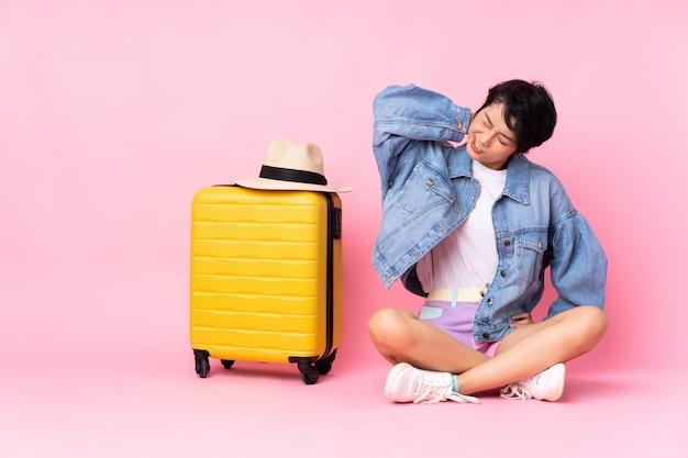 Jeune voyageur femme vietnamienne avec valise assis sur le sol sur rose isolé