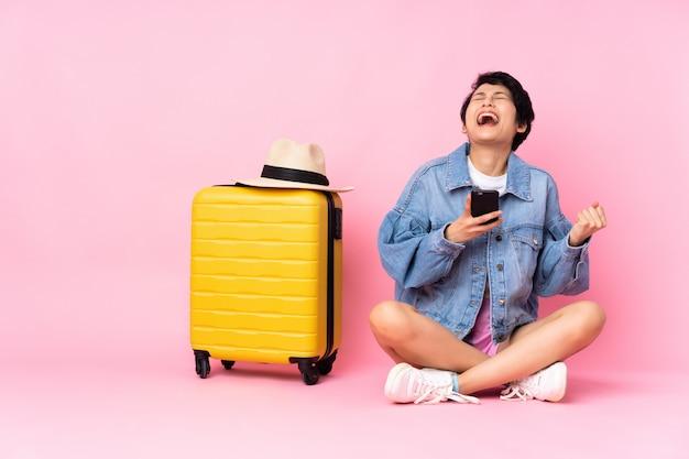 Jeune voyageur femme vietnamienne avec valise assise sur le sol sur un mur rose isolé avec téléphone en position de victoire