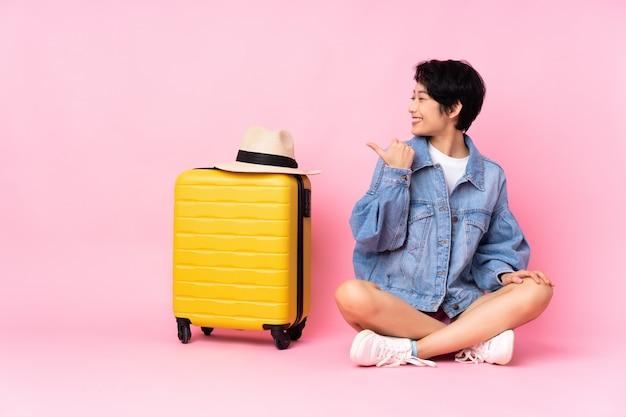 Jeune voyageur femme vietnamienne avec valise assise sur le sol sur rose isolé pointant vers le côté pour présenter un produit
