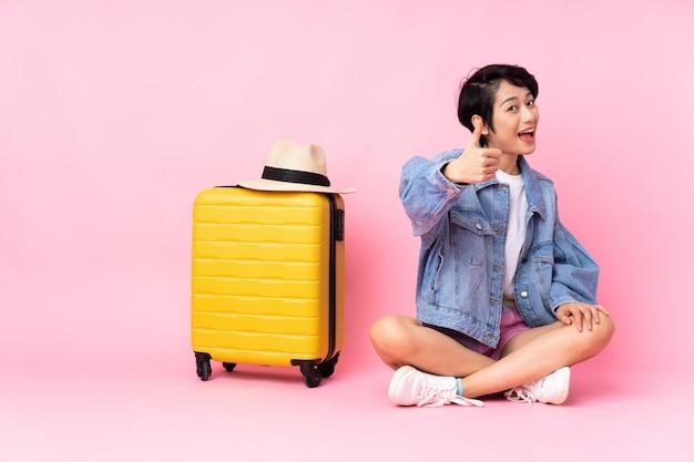 Jeune voyageur femme vietnamienne avec valise assise sur le sol