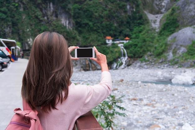 Jeune voyageur fille tenant un téléphone mobile tout en prenant une photo du temple de changchun, taroko, taiwan