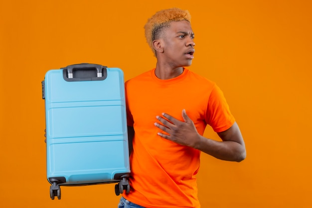 Jeune voyageur garçon portant un t-shirt orange tenant valise à côté confus et surpris de toucher sa tête debout sur un mur orange