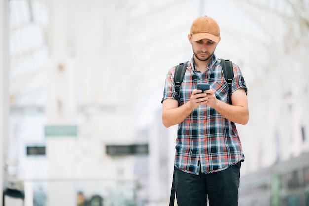 Jeune voyageur à la gare à l'aide d'un téléphone à la gare