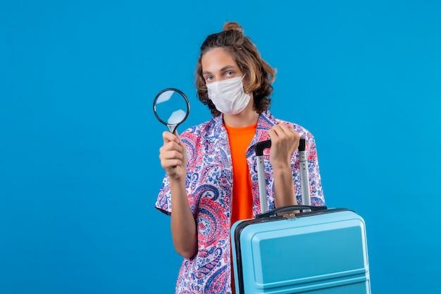 Jeune voyageur guy portant un masque de protection du visage tenant une valise de voyage et une loupe à la confiance debout sur fond bleu