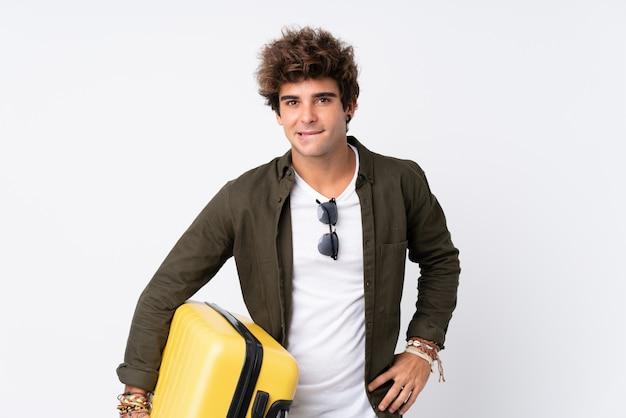 Jeune voyageur homme tenant une valise sur un mur blanc isolé ayant des doutes et avec une expression de visage confuse