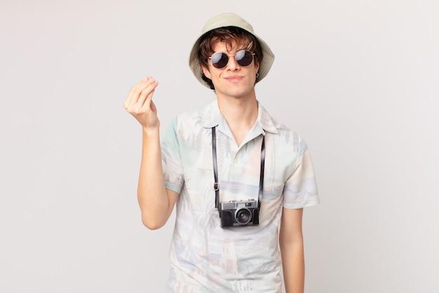 Jeune voyageur ou homme touriste faisant capice ou geste d'argent, vous disant de payer
