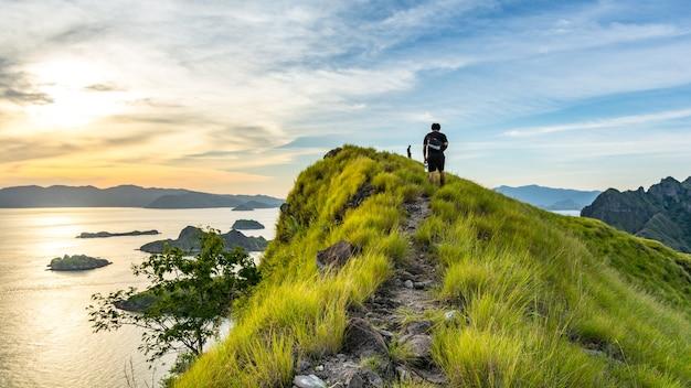 Un jeune voyageur marchant sur la route du sommet de l'île padar au coucher du soleil. komodo nationa