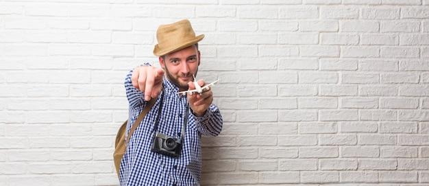 Jeune voyageur portant un sac à dos et un appareil photo vintage gai et souriant pointant vers l'avant.