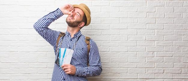 Jeune voyageur portant un sac à dos et un appareil photo vintage regardant à travers une brèche, se cachant et plissant les yeux.