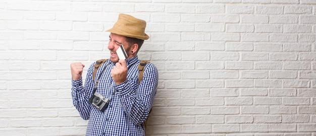 Jeune voyageur portant un sac à dos et un appareil photo vintage très heureux et excité,