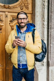 Jeune voyageur portant des vêtements à la mode, debout dans un musée ayant un air heureux d'y être