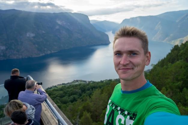 Jeune voyageur prenant selfie sur le dessus avec beau fjord sur fond en norvège.