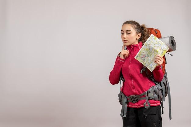 Jeune voyageur réfléchi avec un grand sac à dos tenant une carte