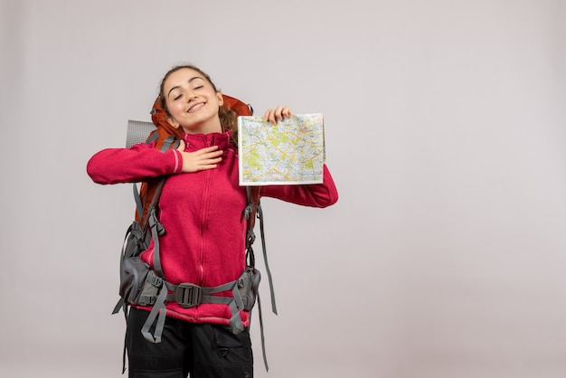 Jeune voyageur satisfait avec un gros sac à dos tenant une carte sur fond gris