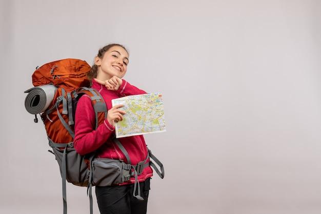 Jeune voyageur souriant avec un gros sac à dos tenant une carte sur fond gris
