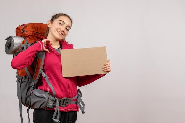 Jeune voyageur souriant avec un gros sac à dos tenant un carton sur fond gris