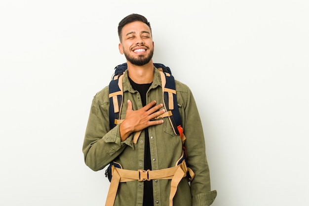 Jeune voyageur sud-asiatique éclate de rire en gardant la main sur la poitrine.
