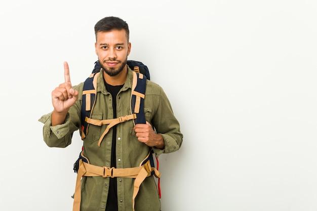 Jeune voyageur sud-asiatique montrant le numéro un avec le doigt.