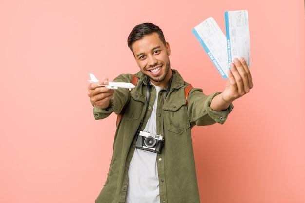 Jeune voyageur sud-asiatique tenant un billet d'avion.