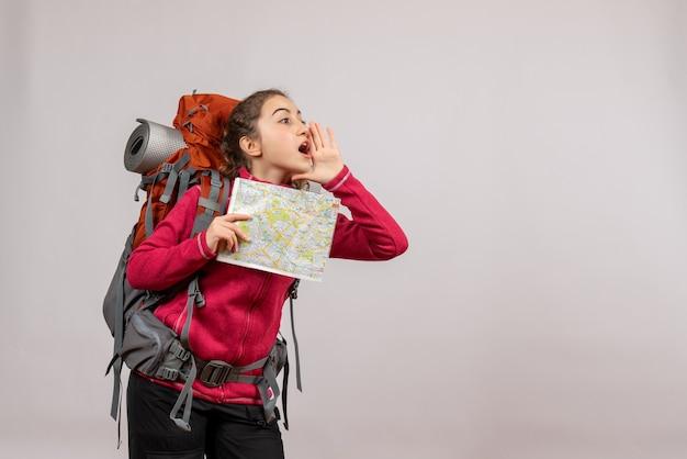 Jeune voyageur vue de face avec un grand sac à dos tenant une carte appelant quelqu'un
