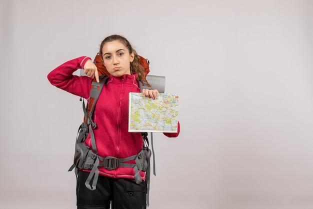 Jeune voyageur vue de face avec un grand sac à dos tenant une carte pointant vers le bas