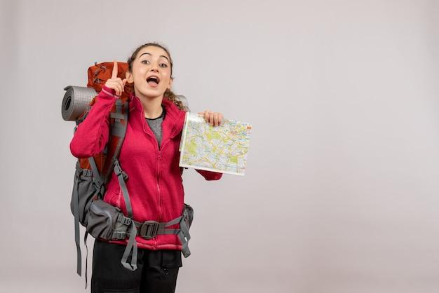Jeune voyageur vue de face avec un grand sac à dos tenant une carte pointant vers le haut