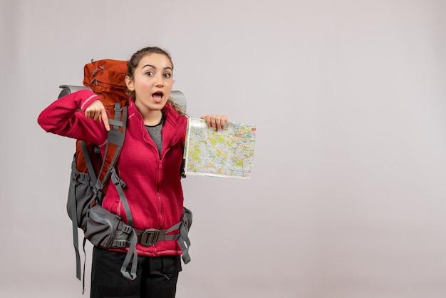 Jeune voyageur vue de face avec un grand sac à dos tenant une carte pointant vers le sol