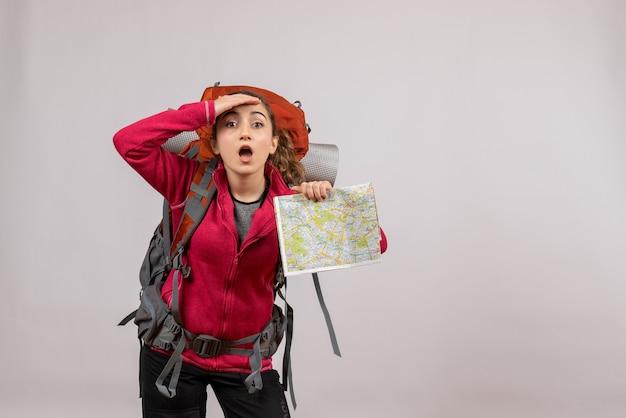 Jeune voyageur vue de face avec un grand sac à dos tenant une carte regardant quelque chose