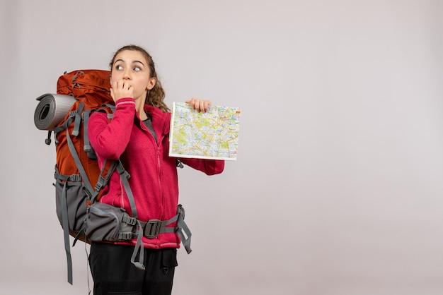 Jeune voyageur vue de face avec un grand sac à dos tenant une carte