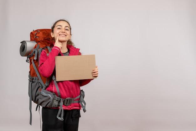 Jeune voyageur vue de face avec un gros sac à dos tenant un carton souriant