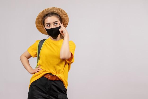 Jeune voyageur vue de face avec sac à dos pensant à quelque chose