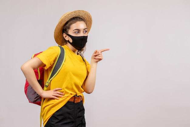 Jeune voyageur vue de face avec sac à dos pointant vers la droite