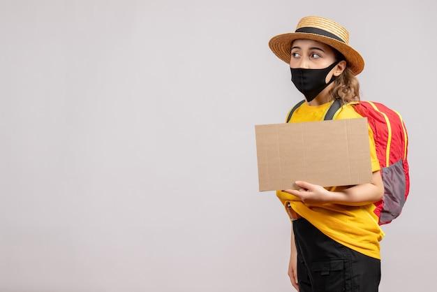 Jeune voyageur vue de face avec sac à dos tenant du carton