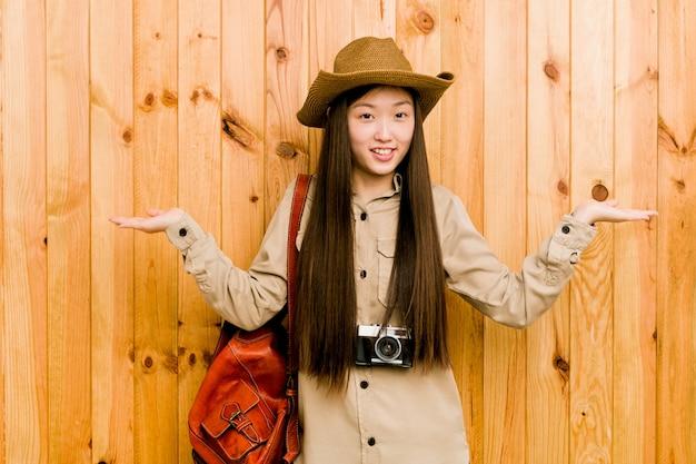 La jeune voyageuse chinoise fabrique une balance avec les bras, elle se sent heureuse et confiante.