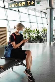 La jeune voyageuse porte un masque de prévention dans un aéroport pendant le vol en attente