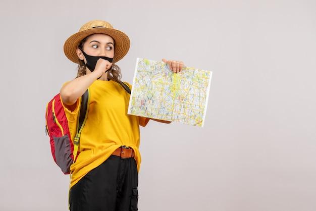 Jeune voyageuse avec sac à dos rouge brandissant la carte sur fond gris