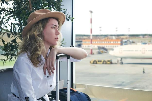 Une jeune voyageuse avec des valises est assise dans la salle d'attente de l'aéroport et elle est triste